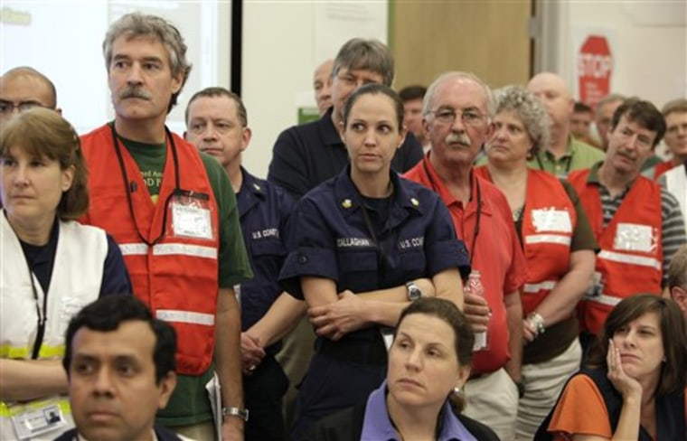BP employees and members of the U.S. Coast Guard in the command center at the Houma Joint Information Center listen to BP Chief Operating Officer Doug Suttles speak about the Deepwater Horizon oil spill in Houma, La., in June.