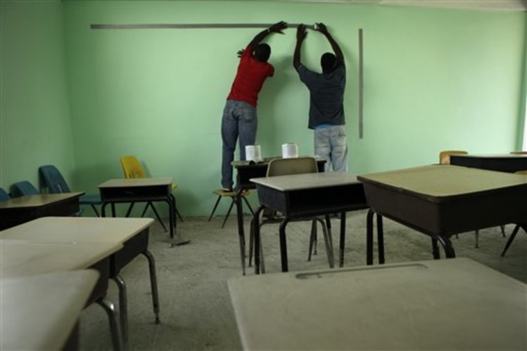 Men use tape to mark off an area to create a blackboard at the Christian Light Ministries school in Port-au-Prince, Haiti, on Aug. 25. In the seven months since the earthquake, the 62-year-old Sherrie Fausey from Jacksonville, Fla., has constructed a new school building for her 200 students. She's also tripled the salaries for her 22 teachers.