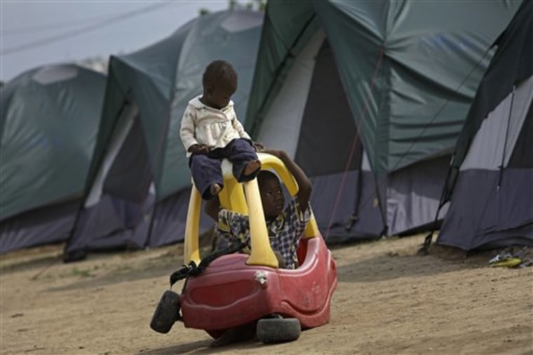 Two Haitian children play with a broken toy car at a camp for earthquake survivors set up by Michael Capponi, a Miami property developer, in Port-au-Prince, Wednesday. A strong earthquake struck Haiti on Jan. 12.