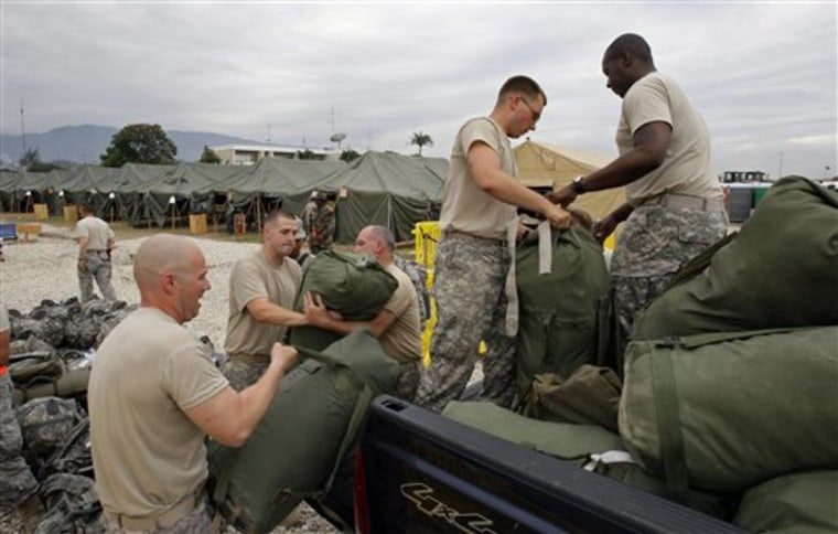 U.S. Army soldiers load their duffels prior to their departure from Port-au-Prince, Haiti, on Sunday.