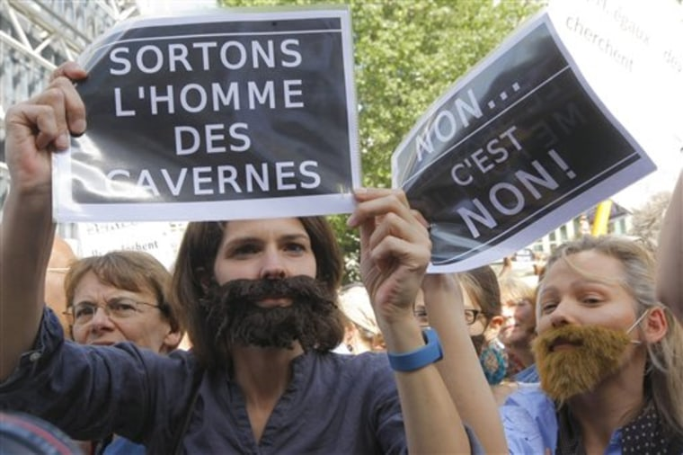 Women hold signs and wear false beards as they ptotest against sexism, rape and sexual crimes in Paris on May 22. French women's groups outraged by the political and media reaction to the sexual assault allegations against Dominique Strauss-Kahn organized the protest.
