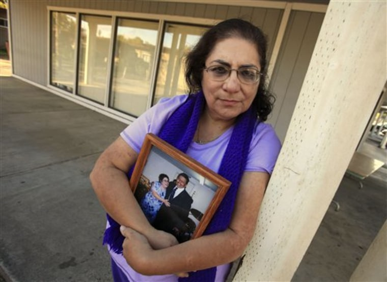 Karen Carrisosa holds a photo of her and her husband, Larry, at the site where he was killed in Sacramento, Calif. Carrisosa became concerned when officials found a Facebook posting from Corcoran State Prison inmate Fredrick Garner, who is serving a 22-year, involuntary manslaughter sentence for killing Larry 11 years ago.