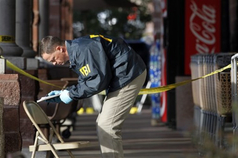 An FBI agent on Jan. 10 writes down information as he looks around the area at a local Safeway in Tucson, Ariz., where Rep. Gabrielle Giffords, D-Ariz., was shot, two days after a mass shooting there left six dead.
