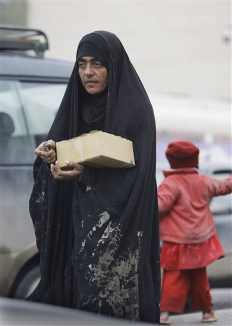 An Iraqi woman and her daughter sell chewing gum in the rain in Baghdad, Iraq, Sunday, Jan. 30.