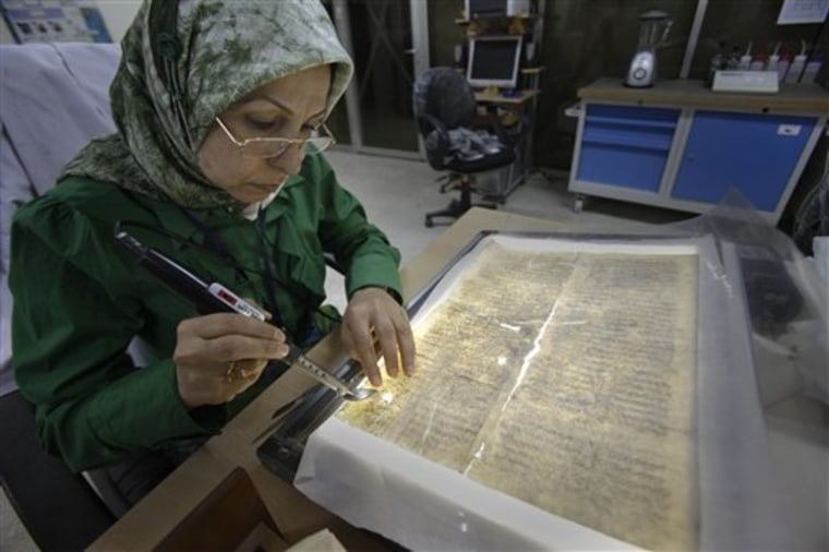 Alaa Jassim, a member of the library restoration staff, works on a damaged document at the Iraq National Library and Archives in Baghdad. A trove of Jewish books and other materials, rescued from a sewage-filled Baghdad basement during the 2003 invasion and now stored at the National Archives and Records Administration in College Park, Md. near Washington, is now caught up in a tug-of-war between the U.S. and Iraq.