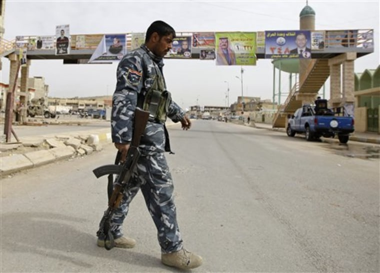 An Iraqi policeman walks past campaign posters for candidates in Iraq's March 7 national election, in Ramadi on Tuesday.
