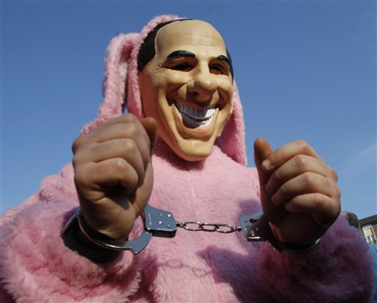 A demonstrator wears a mock mask of Italian Premier Silvio Berlusconi, dressed as a pink rabbit with handcuffs during a protest outside Berlusconi's private residence, in Arcore, Italy, on Sunday to demand his resignation.