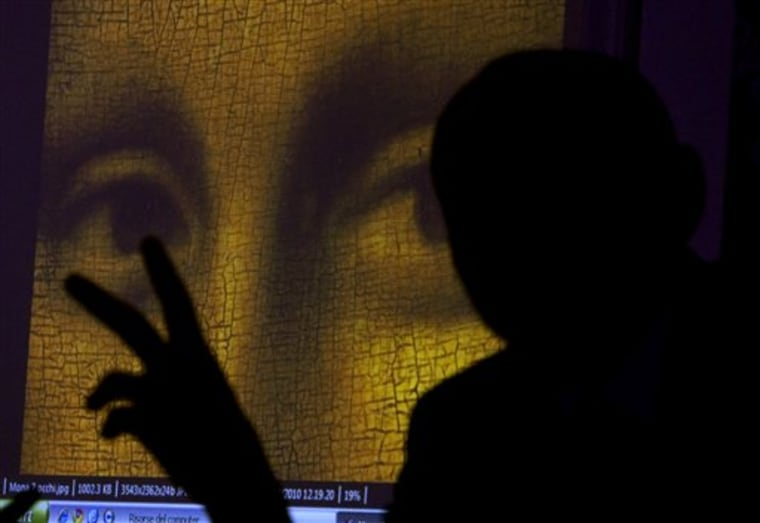 "Art historian and researcher Silvano Vinceti, silhouetted, gestures as an image showing the detail of the eyes of Italian artist Leonardo da Vinci's ""Mona Lisa"" painting is projected in background during a February news conference in Rome. Italian researchers have announced a plan to dig up bones in a Florence convent in hopes of identifying the remains of a Renaissance woman long believed to be the model for the Mona Lisa."