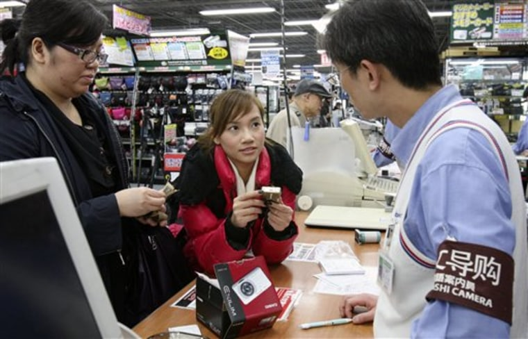 Chinese customers speak with a salesclerk as they buy a compact digital camera at Yodobashi Camera in Tokyo's Akihabara electronics district. For years, Japanese auto and electronics companies have been expanding in China as its economy boomed to offset slow growth at home.