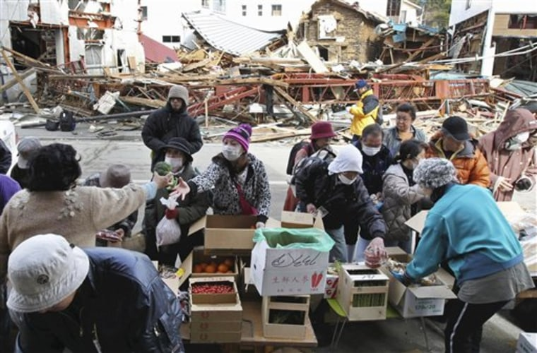 People shop for produce at a makeshift store in a devastated area of Kesennuma, in northern Japan, on Sunday.