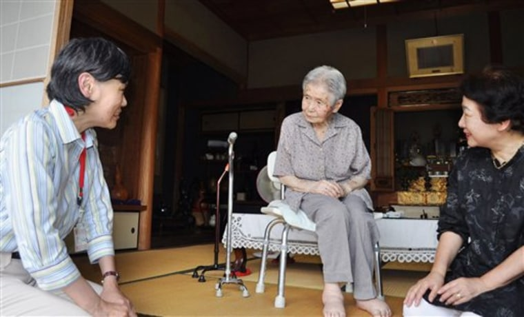 A Kobe city official, left, visits 100-year-old Mitsue Watase, center, at Watase's home on Tuesday. Officials started a door-to-door survey on the whereabouts of centenarians.