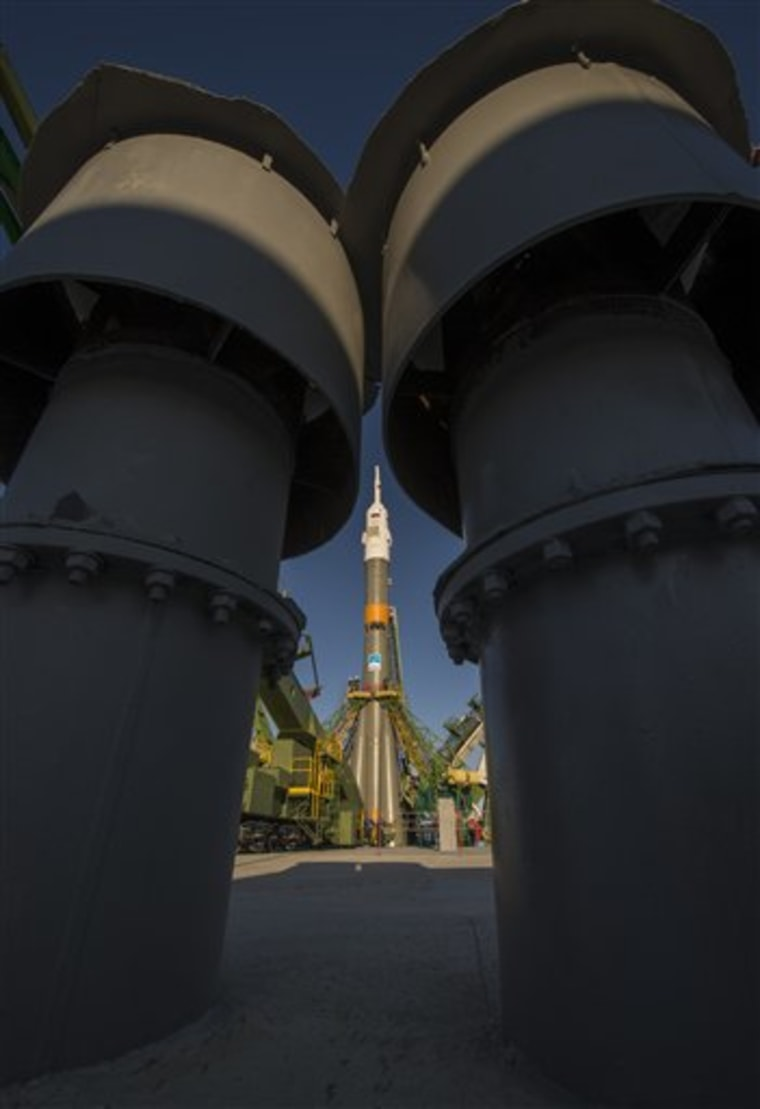 The Soyuz rocket is erected into position after being rolled out to the launch pad by train, on Sunday, Oct. 21, 2012, at the Baikonur Cosmodrome in Kazakhstan.