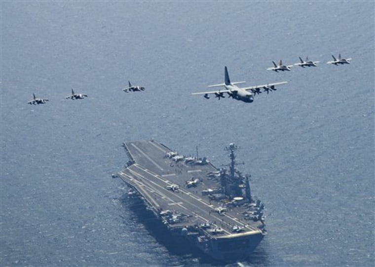 Planes fly in formation over the aircraft carrier USS George Washington in the seas east of the Korean peninsula on July 27. U.S. and South Korean ships got into position in the Yellow Sea on Sunday for the four-day exercise, said Cmdr. Jeff Davis, spokesman for the 7th Fleet in Yokosuka, Japan.
