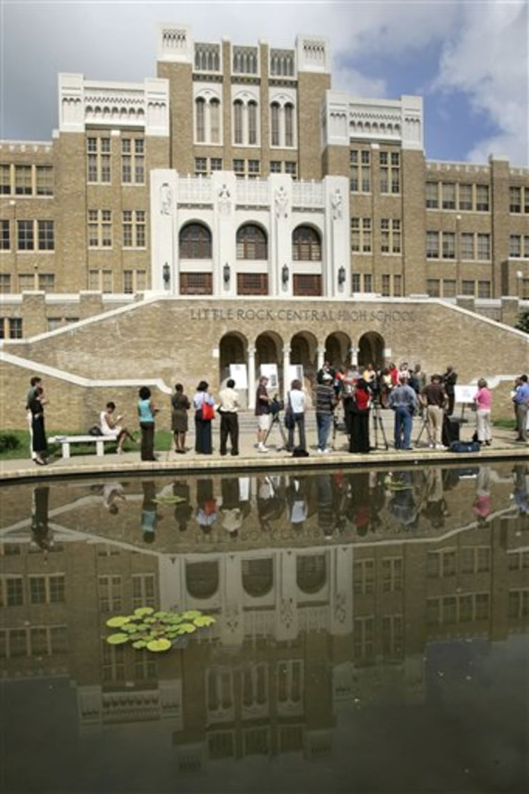 The image of Little Rock Central High School is reflected in a pond during a news conference in Little Rock, Ark., on July 16, 2007. Nine black students desegregated the school in September 1957.