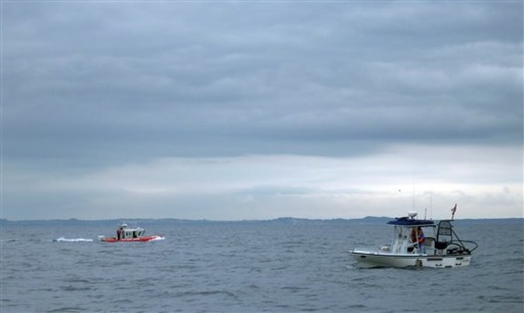 Members of The United States Coast Guard, left, and the Mason County Sheriff's office, right, search the waters of Lake Michigan after a medical transport plane carrying five people to the Mayo Clinic crashed into the lake on Friday.