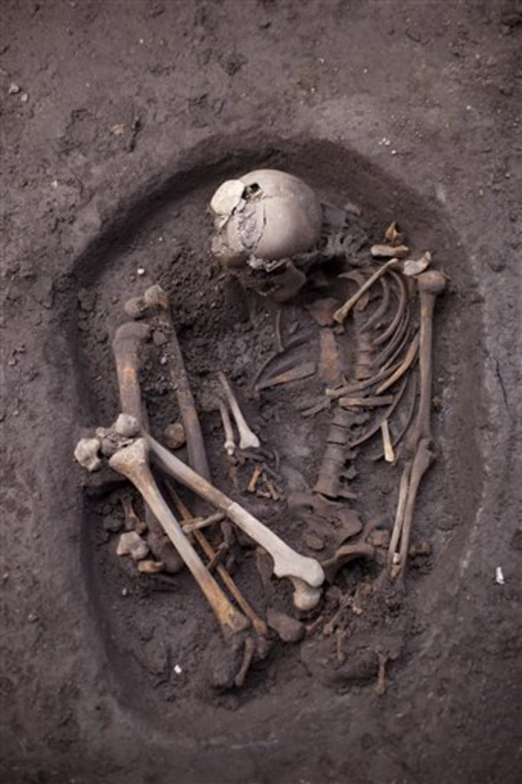 An unearthed skeleton dating back about 700 years is seen at a recently discovered archeological site in Mexico City, Friday, July 13, 2012. According to Mexico's National Institute of Anthropology and History, INAH, the site is about 700 years old and is a neighborhood of Tepaneca merchants. (AP Photo/Alexandre Meneghini)
