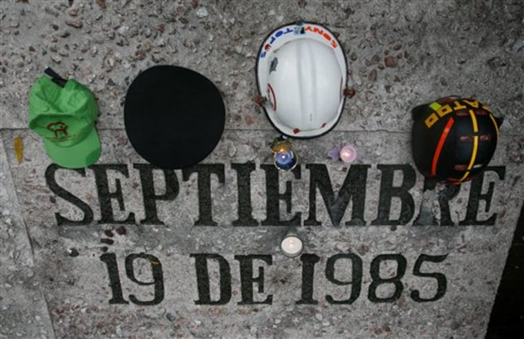 "Helmets and caps of ""Topos"" are seen atop the 1985 earthquake's memorial, during a ceremony to commemorate its 25th anniversary in Mexico City, Sunday, on Sept. 19."