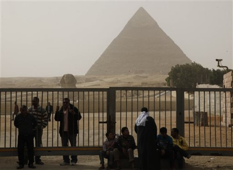 Egyptian tourist guides and security on Saturday sit near the pyramids in Giza, Egypt. The military has closed the pyramids to tourists following unrest in Cairo, the nation's capital.