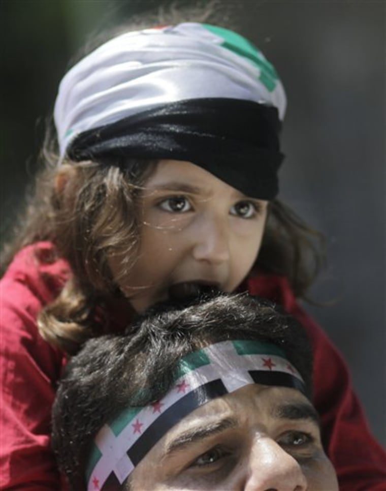 A Syrian wears a Syrian independence flag headband as he carries a young girl on his shoulders during anti-Syrian regime protest outside the Arab League headquarters in Cairo, Egypt, on Sunday.