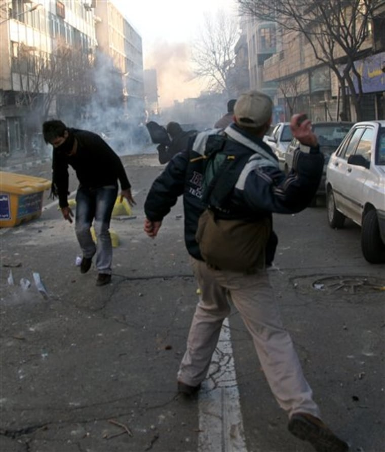 This photo, taken by an individual not employed by the Associated Press and obtained by the AP outside Iran, shows Iranian protesters throwing stones at anti-riot police Monday during an anti-government protest in Tehran, Iran.