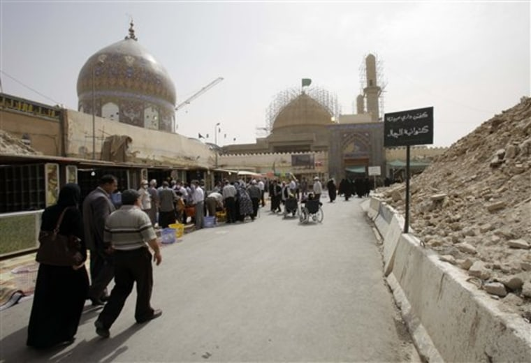 Scaffolding remains around the dome and minaret of the al-Askari shrine as Shiite pilgrims pay a visit in Samarra, north of Baghdad, Iraq.