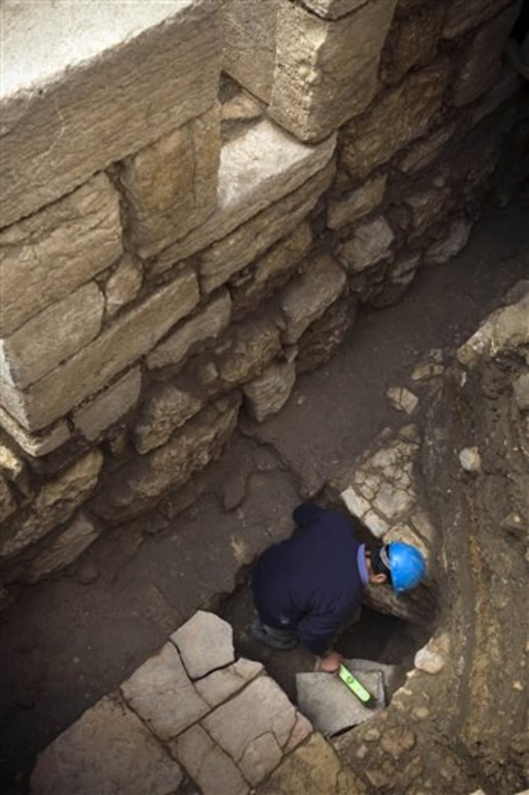 A worker cleans a stone in a 1,500-year-old street located 4.3 meters (14 feet) below ground level, revealed by the Israeli Antiquities Authority in the old city of Jerusalem.