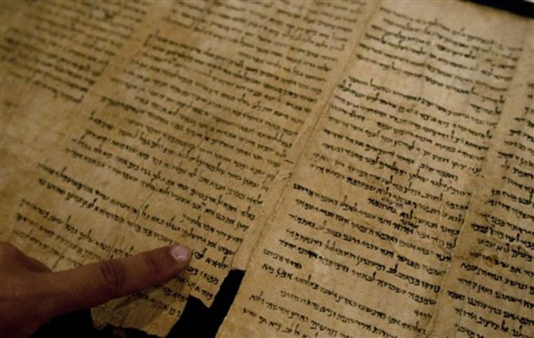 "An Israel Museum worker points at the word ""Jerusalem"" written in a part of the Isaiah Scroll, one of the Dead Sea Scrolls, inside the vault of the Shrine of the Book building at the Israel Museum in Jerusalem on Monday."