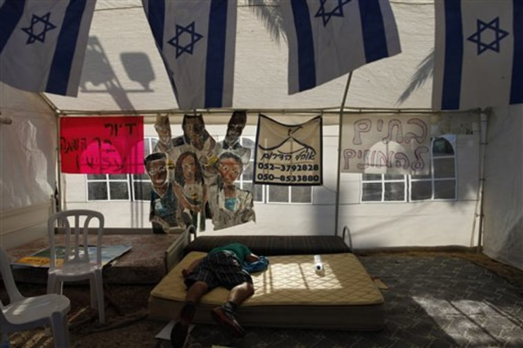 "An Israeli man rests in a tent in a Beersheba encampment set up to protest against the rising costs of living. The signs read ""Homes for the crowds"" and ""Affordable housing now."""
