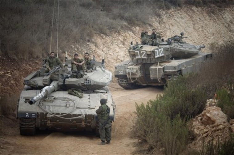Israeli soldiers sit on a tank Wednesday near the site of an exchange of fire between Israeli and Lebanese troops.