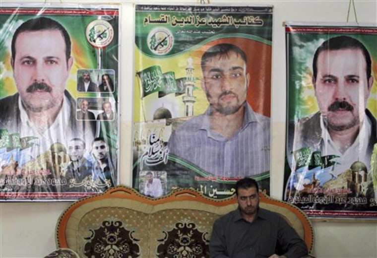 Palestinian Fayeq al-Mabhouh sits in front of posters of his brother and Hamas commander, Mahmoud al-Mabhouh, left and right, who was assassinated in Dubai, and Hamas member Mohammed Hussein Mabhouh.