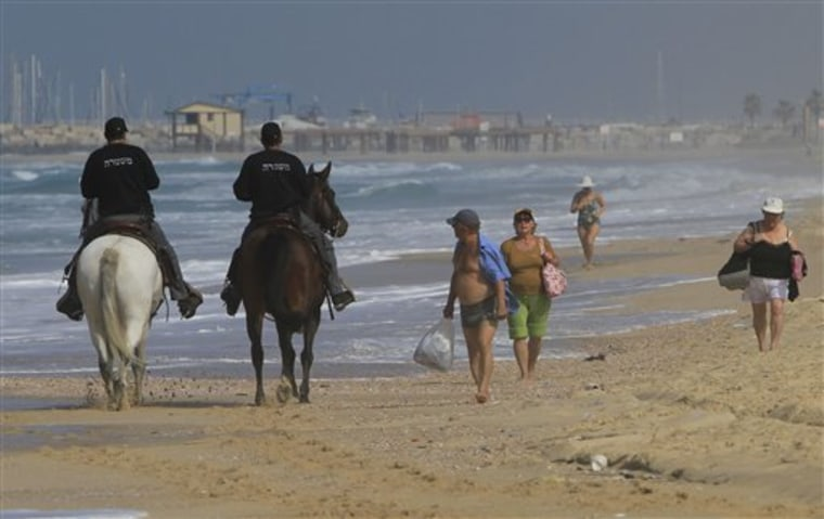 Israeli policemen, riding on horses, patrol along the beach in the southern Israeli town of Ashkelon, near the Gaza border, on Tuesday. On Monday, at least two barrels full of explosives washed up on Israeli beaches north of Gaza.