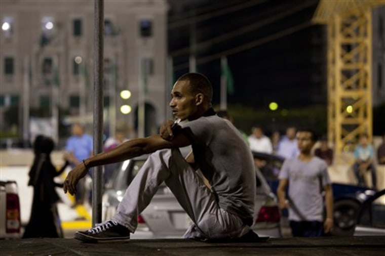 In this photo taken on a government-organized tour, a young man sits at the main Green Square Monday in Tripoli, Libya.