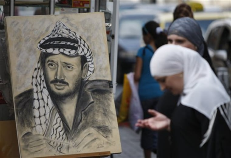 A Palestinian woman stands by a drawing of late Palestinian leader Yasser Arafat, displayed on a street corner in the West Bank city of Ramallah on Thursday. Palestinian President Mahmoud Abbas has said he's willing to exhume the body after doctors said they found elevated levels of the radioactive agent polonium-210 on clothing reportedly worn by Arafat before his death in November 2004.