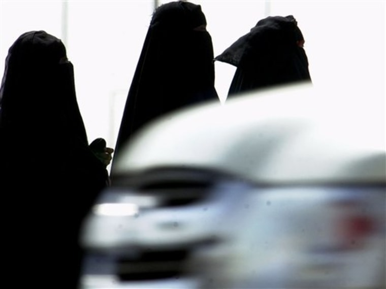 Saudi women walk past cars in a Riyadh, Saudi Arabia, street.