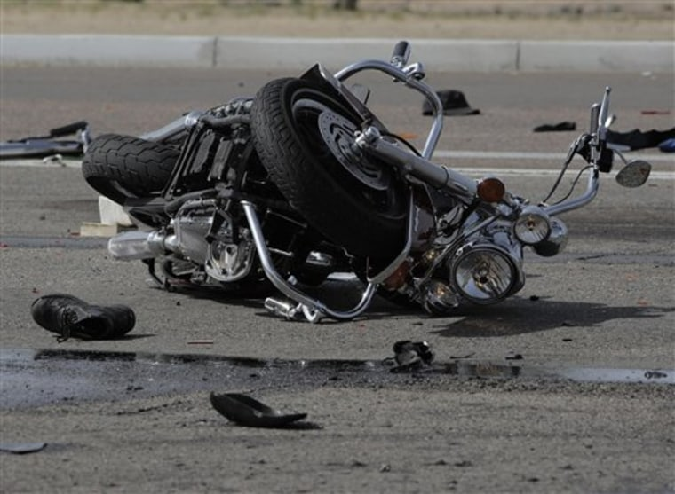 A wrecked motorcycle lies at the the scene of a multi-motorcycle and trash truck accident on the Carefree Highway in Phoenix, Ariz., March 25, 2010. Three people riding motorcycles were killed and six others critically injured when several bikes were struck by a truck hauling garbage on the Carefree Highway in north Phoenix.