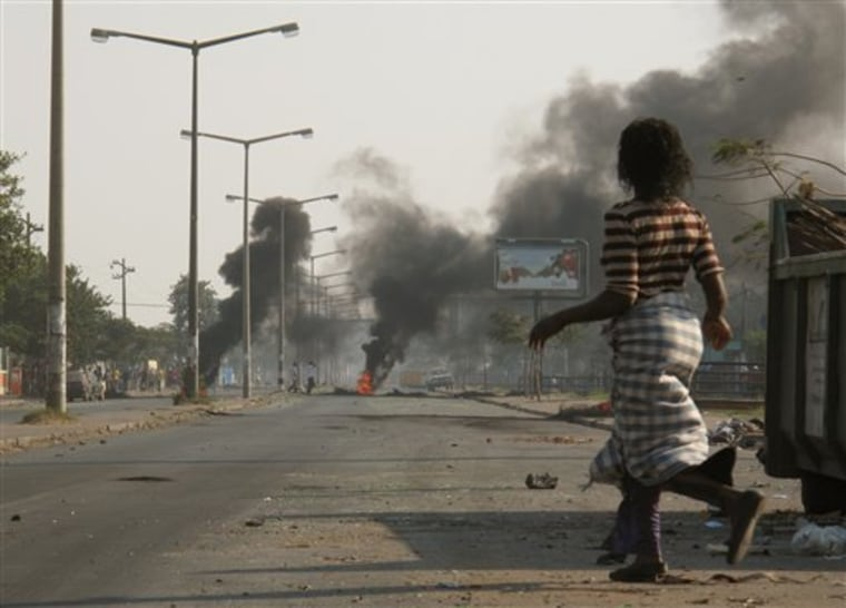 A woman passes near burning tires in a street in Maputo, Thursday Sept. 2, 2010 a day after police opened fire on stone-throwing crowds who were protesting rising prices in this impoverished country.