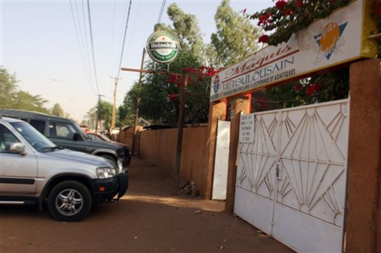 Cars sit parked outside the front gate of the Toulousain restaurant, where witnesses say two French nationals were kidnapped at gunpoint late Friday by turbaned men, in Niamey, Niger. A witness was dining inside when he says two men walked in, pulled out guns and told the French citizens to follow them. Outside, he says, two more men were waiting and they forced them into a truck and sped off.