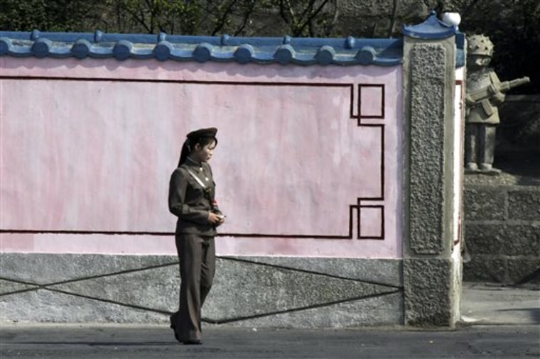 A female North Korean soldier walks along a wall to a compound in North Korea's Sinuiju seen from a boat along the Yalu river near the Chinese border town of Dandong in China's northeastern Liaoning province, on May 23.
