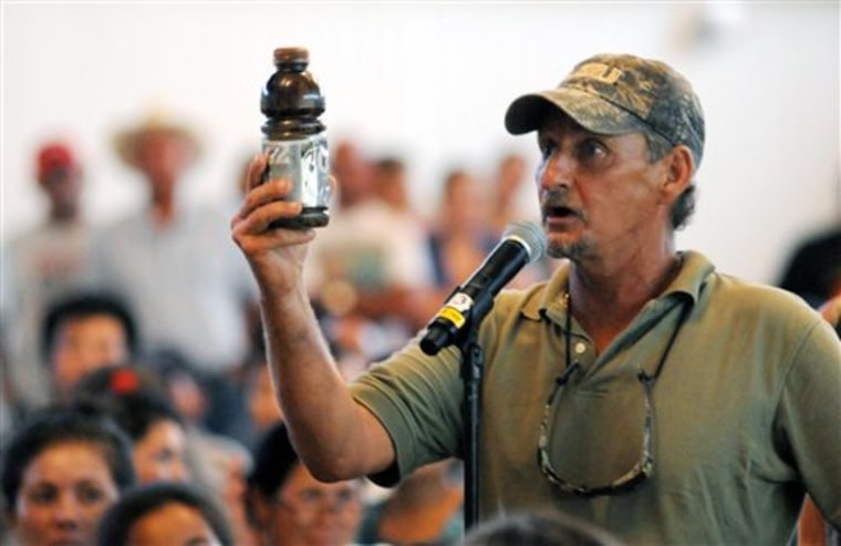 A.C. Cooper, vice president of the Louisiana Shrimp Association, holds a bottle of oil as he pleads to Ray Mabus, U.S. secretary of the Navy, to ensure the safety of Louisiana seafood during a town hall meeting for fishermen and residents in Buras, La.