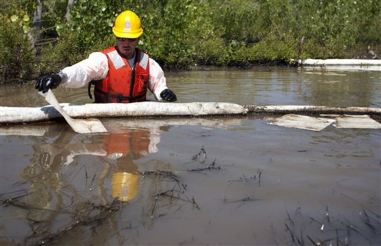 A cleanup worker uses oil absorbent materials on the Yellowstone River in Laurel, Mont., on Wednesday.