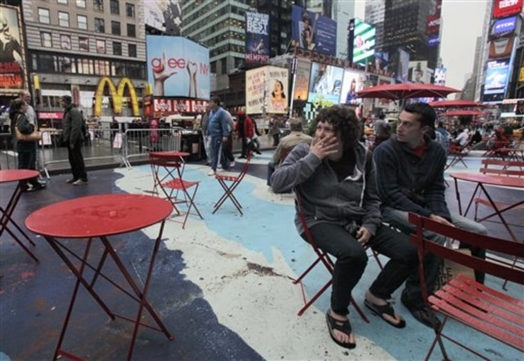 A woman smokes a cigarette in New York's Times Square. A new law bans smoking in New York City's 43 square miles of urban parks and other public places. The law will be enforced with a $50 fine per violation.