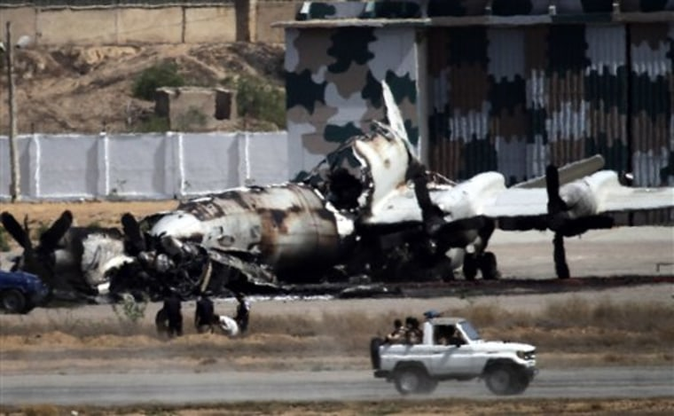 Pakistani troops drive past a wreckage of a gutted aircraft destroyed by militant attacks at a Pakistan Navy base in Karachi, Pakistan, on May 23. Facing a surge in violence after the killing of Osama bin Laden, Pakistanis are taking comfort in conspiracies theories that allege Indian or American agents — not fellow Muslim countrymen — are behind the attacks.