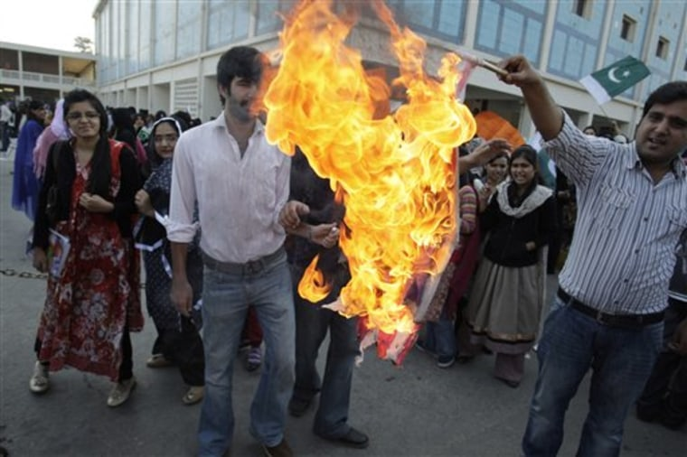 Protesters burn a representation of a U.S. flag during a rally in Lahore, Pakistan, on Wednesday.