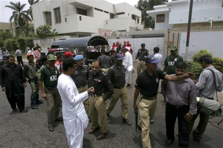 Pakistani police officer gather at the site of an explosion outside the office of International Committee of the Red Cross in Karachi, Pakistan on Saturday, June 25, 2011.