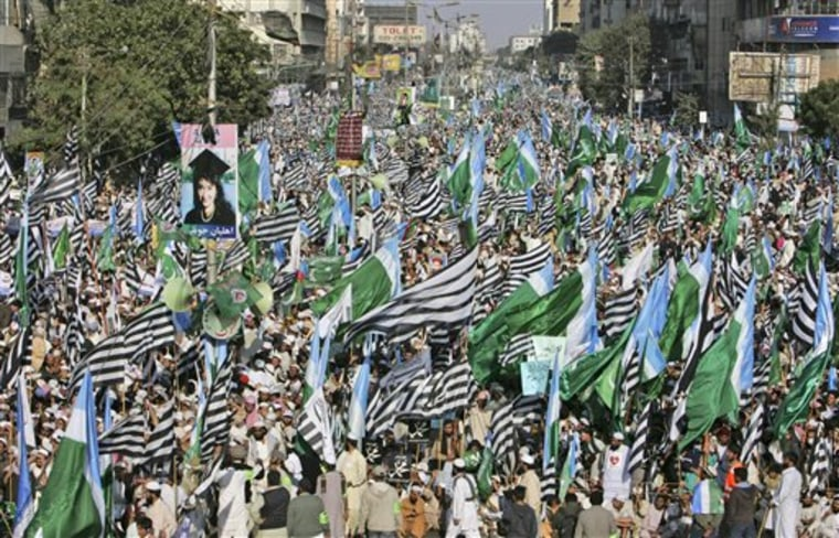 Supporters of Pakistani religious parties wave flags during a rally to protest against any attempts to modify blasphemy laws, in Karachi, Pakistan, on Sunday. Tens of thousands of demonstrators have marched in Pakistan's largest city in opposition to any change to blasphemy laws and to praise the man charged with murdering the provincial governor who opposed the legislation.