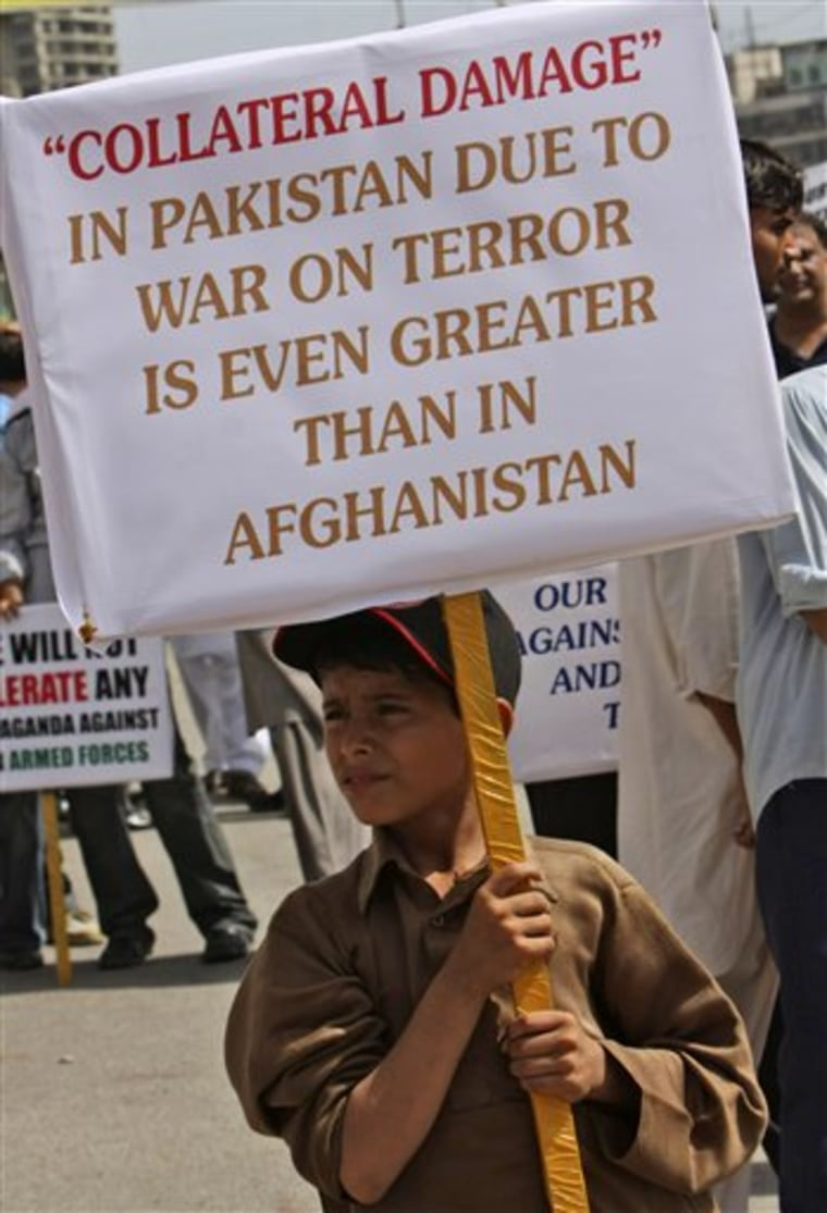 A Pakistani boy holds up a placard during a rally organized by members of a civil society in support of Pakistan's army and the Inter-Services Intelligence agency, ISI, in Karachi, Pakistan, on Saturday. Members of Pakistan's Parliament slammed the United States on Saturday for the raid that killed al-Qaida chief Osama bin Laden on their soil.