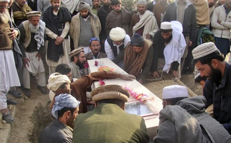 Pakistani relatives and mourners gather around the coffin of a police officer who died Wednesday in a suicide attack in Bannu, during his funeral procession in Lakki Marwat, Pakistan, on Thursday. A suicide car bomber on Wednesday killed many people in an attack on a police station and adjoining mosque in the northwest, showing the threat militants pose there despite repeated offensives by the Pakistani army over the last 2 1/2 years.