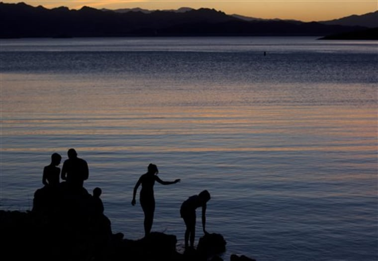 Jeffery Serrano of Henderson, Nev., second from left, helps his kids fish at twilight at the edge of Kingman Wash at Lake Mead National Recreation Area, Ariz.