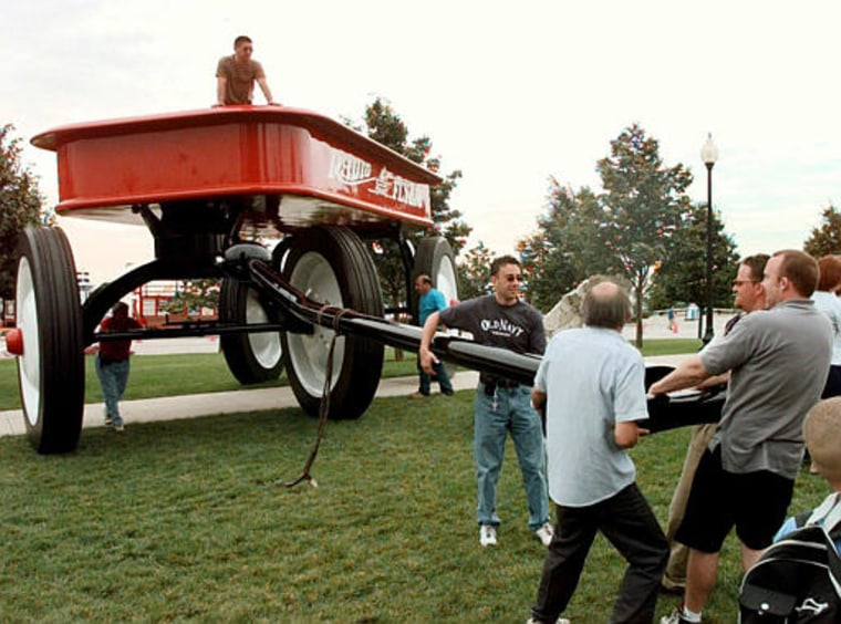 Workers pull a giant Radio Flyer wagon into place at near Navy Pier in Chicago in June 2000. The world's biggest wagon was made by Chicago-based  Inc. to mark its 80th anniversary. It now plans to manufacture the iconic American toy in China, and will lay off nearly half of its 90 employees.