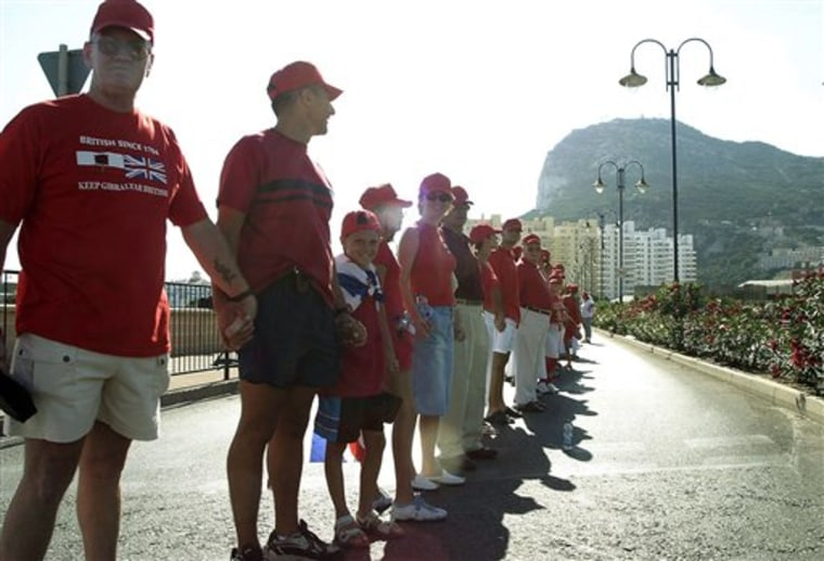 Gibraltarians link hands Wedbesday to form a human chain around their tiny colony — a show of unity by the British subjects but also a display of solidarity against Spain, from whom this peninsular tip was captured in 1704.